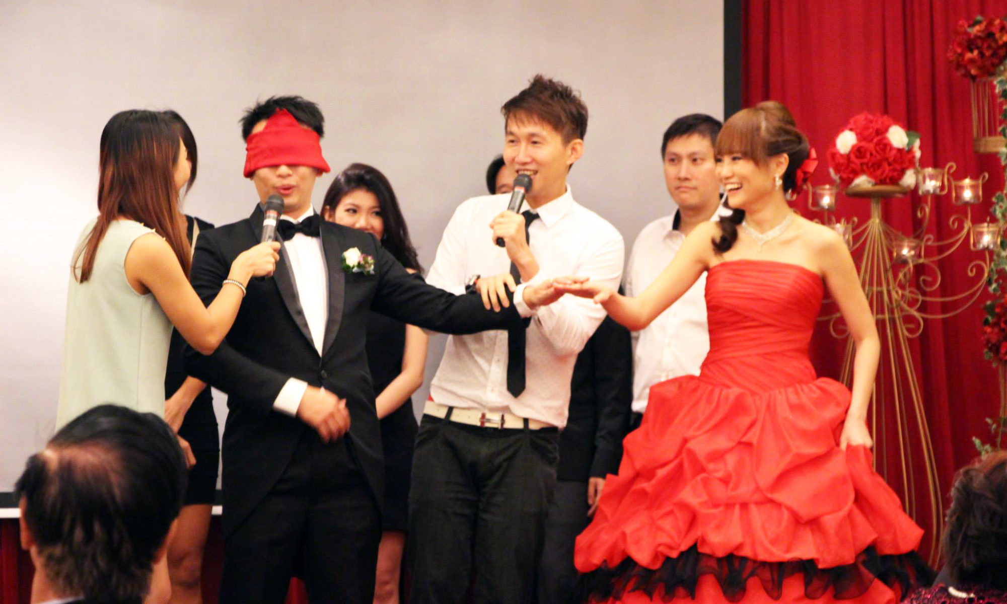 Emcee Jim Koh playing games with wedding couple
